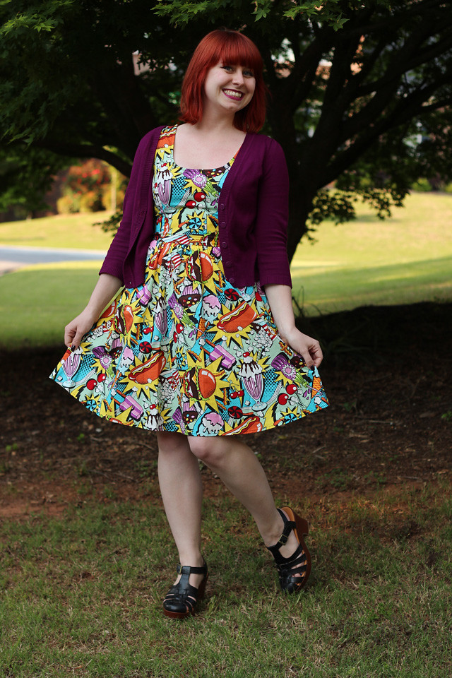 Purple Cardigan, Colorful Novelty Print Dress, and Black Sandals