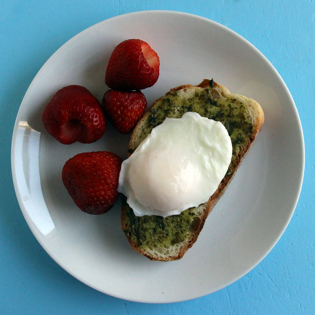 Monday breakfast -- poached egg on pesto toast, strawberries