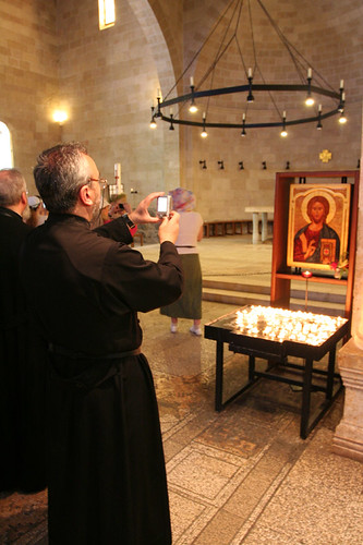 priest taking a digital photo of Jesus