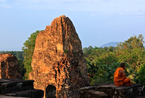 A Buddhist monk looks away from the sunset on top of Prae Roup Temple