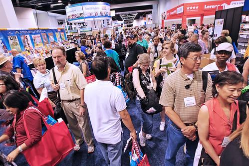 Crowded exhibit hall floor full of people.