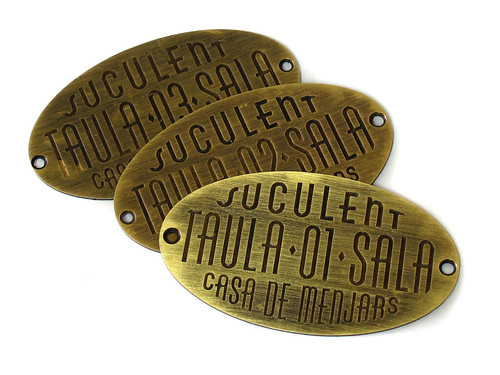 Antique brass engraved plaques to identify restaurant tables