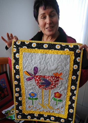 Eyes wide shut, with that expression! Debra Fitzgerald shows off a small fabric art from her collection, quilt surrounded by eggs, Lake Otis, Anchorage, Alaska, USA by Wonderlane