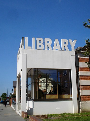 A conservatory-style extension at the front of a redbrick library.  The walls have floor-to-ceiling windows and the white facade of the building is topped with standalone white letters reading 'LIBRARY'.  The sky is a clear deep blue.