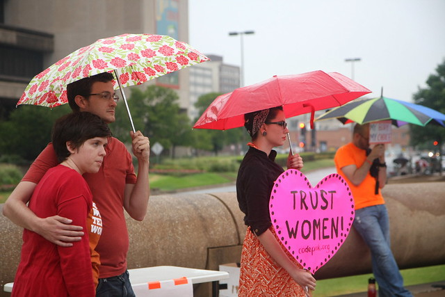 "Protesters in texas hold a sign that says ""trust women"""