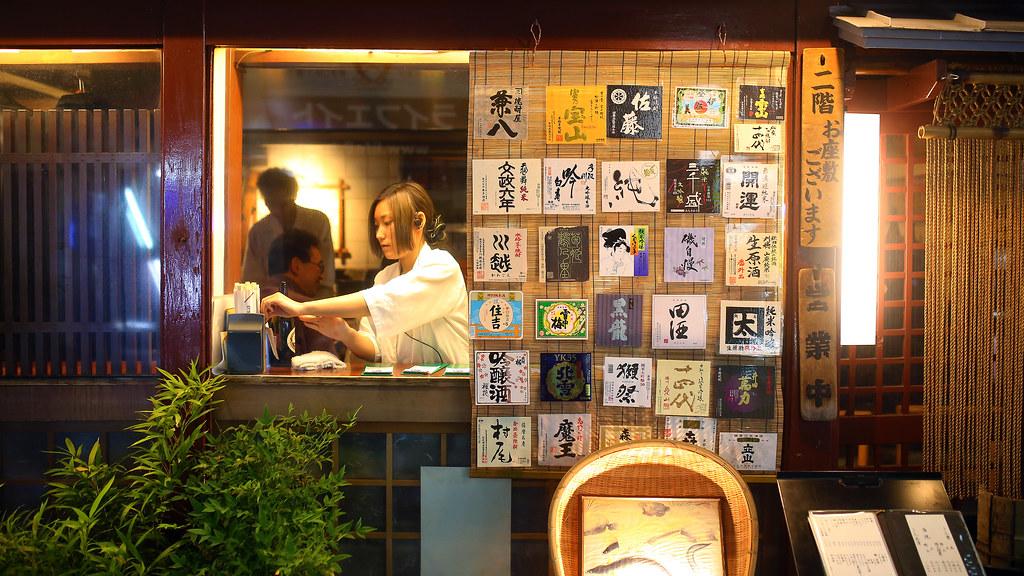 歌舞伎町 Tokyo, Japan / Sigma 35mm / Canon 6D 在路上看到一間店外有好多酒的標籤,正要拍的時候剛好服務生在窗邊準備外帶的餐點,就這樣一起放入畫面中。  我發現很喜歡把畫面拍的每個地方最好都可以慢慢的看。  Canon 6D Sigma 35mm F1.4 DG HSM Art IMG_9443_16x9 Photo by Toomore