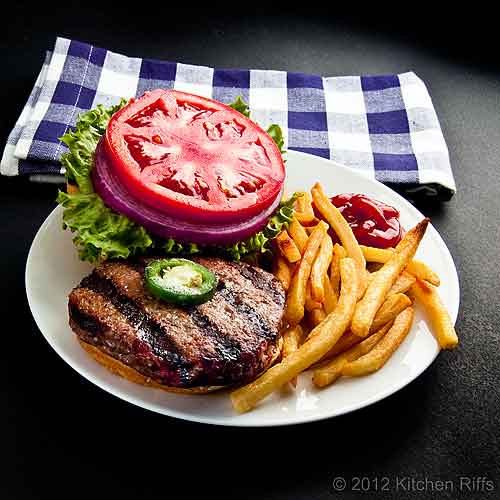 Grilled Hamburger, Bun, and Garnish on Plate with Fries