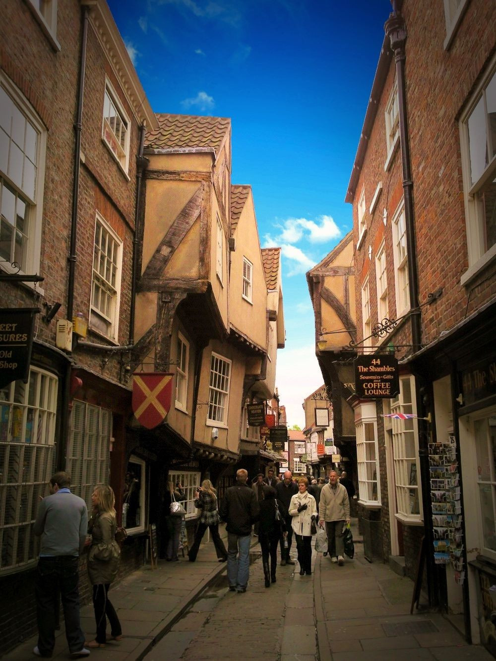 The timber-framed buildings overhang the street. Credit MuleAthon