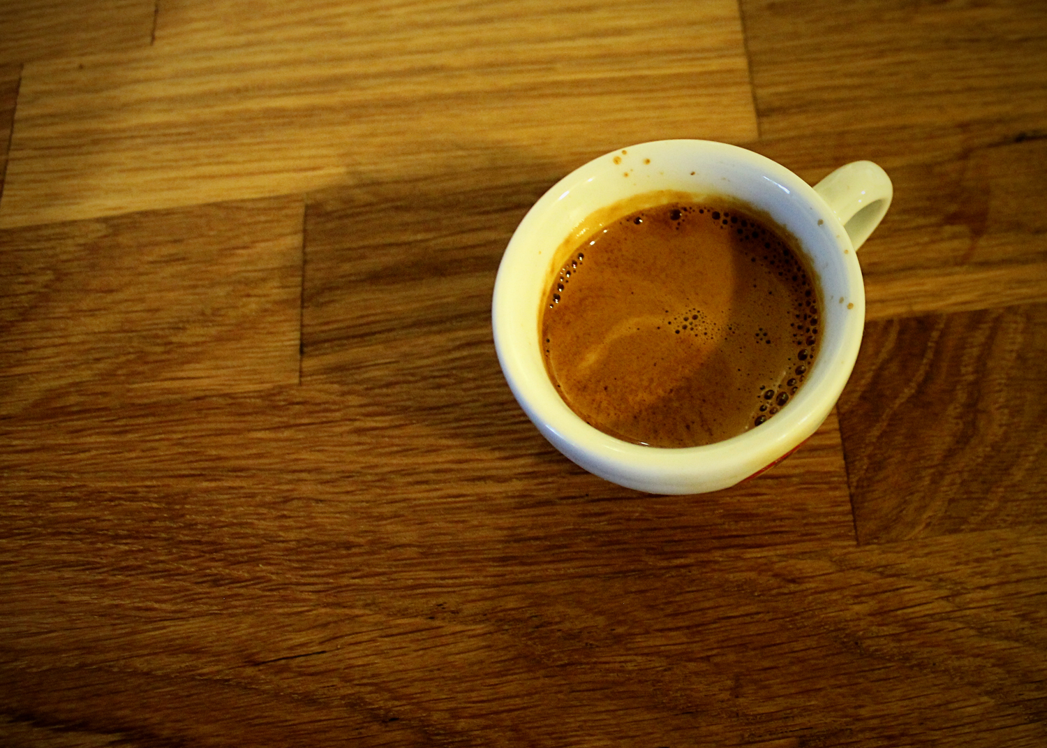 A shot of espresso in a small white mug pulled from a La Pavoni Espresso Machine