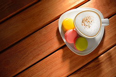 A cup of cappuccino and pastries(macaron) on old w…