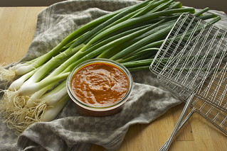 Charred spring onions with salsa romesco