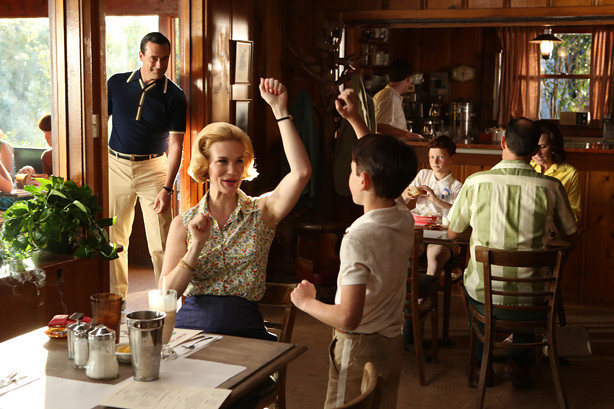 Betty, arm raised, sings with Bobby; Don peers in from background