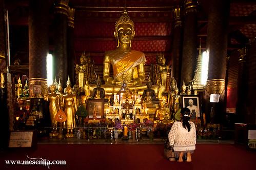 Dona resant al Buda del temple de Wat Mai, a Luang Prabang