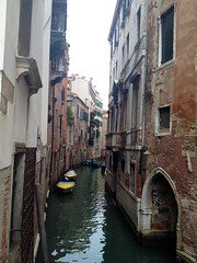 tourism(0.0), gondola(0.0), alley(0.0), infrastructure(0.0), town(1.0), vehicle(1.0), body of water(1.0), channel(1.0), facade(1.0), canal(1.0), boat(1.0), waterway(1.0),