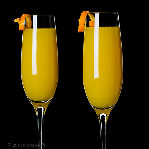 Mimosa Cocktails with orange twist garnish, black background