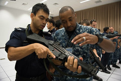 Gunner's Mate 1st Class Michael Davis receives instruction from a Singaporean Coast Guard inspector during a visit, board, search and seizure training brief July 17 as part of a compliant boarding exercise for CARAT Singapore. (U.S. Navy photo by Mass Communication Specialist 3rd Class Karolina A. Oseguera)