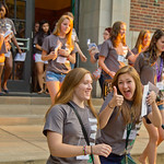 13-013 -- Alyssa Marie Berry gives a thumbs-up as she and Emma Alcock leave Presser Hall after the New Student Convocation.