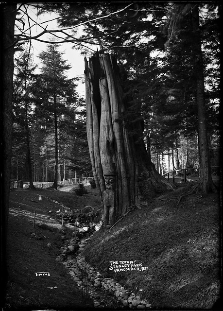 Totem figure by a tree in Stanley Park. VPL7289