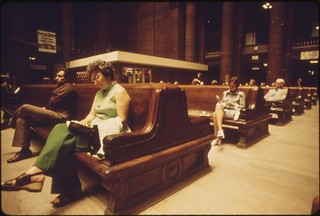 Passengers sit on massive wooden benches which fit in with the architecture of the cavernous Chicago Union Station, June 1974