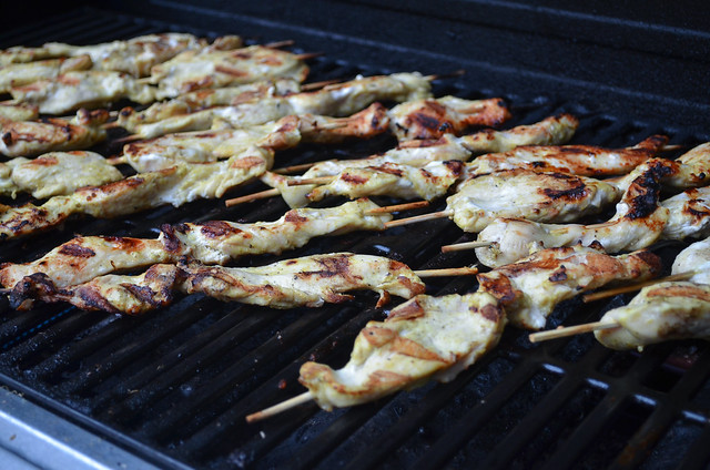 The chicken skewers are arranged on a grill.