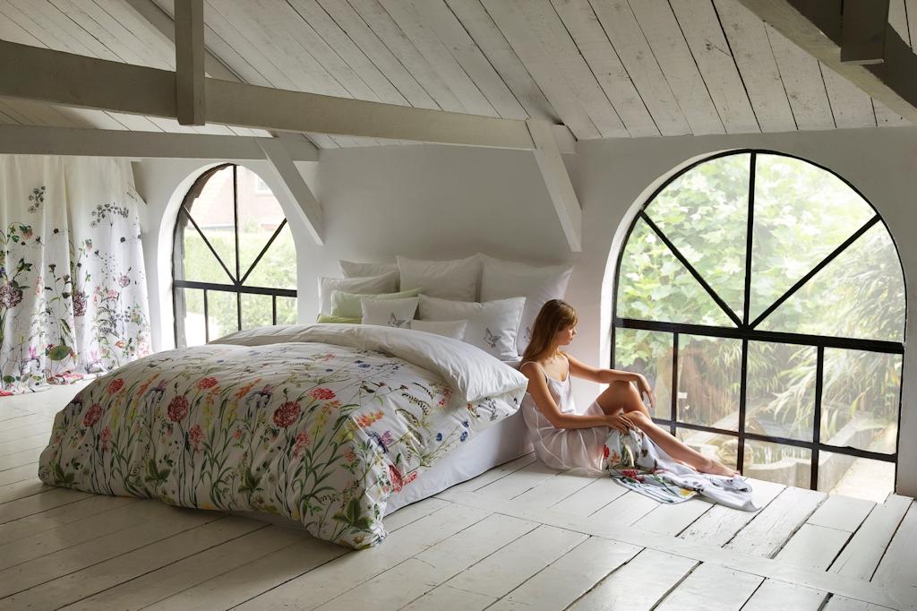 Op de grond zittende jongedame die tegen het bed aan leunt en via het grote raam naar buiten kijkt.