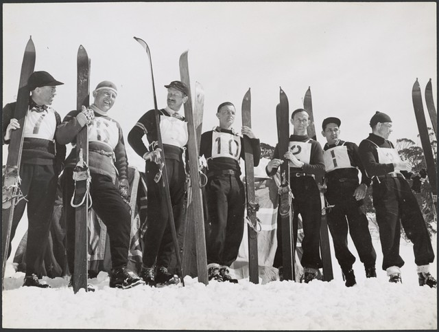 Seven male skiing competitors standing on the slopes holding their ski gear, Snowy Mountains Region, New South Wales, ca. 1942.
