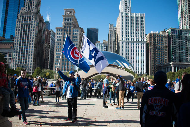 Man holding Chicago Cubs flags in front of Chicago bean during Cubs World Series celebration