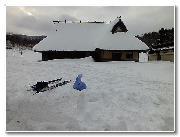 雪に埋もれる山麓庵.屋根の雪が落ちて周囲に高く積もっている.