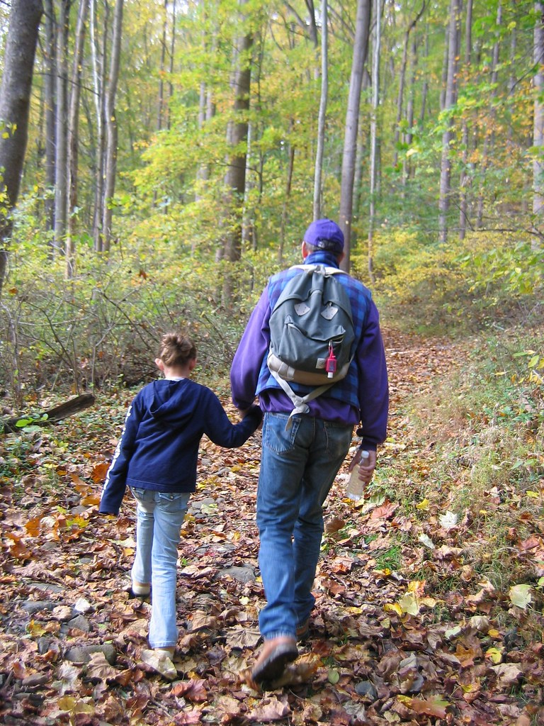 Father and daughter hold hands on a hike