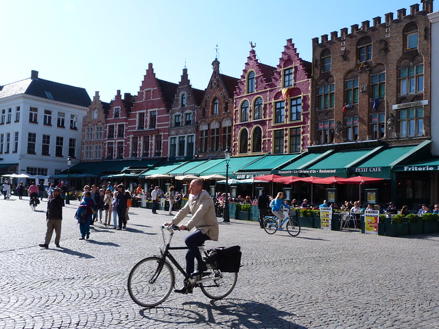 Hombre en bicicleta en la Plaza Markt de Brujas (Flandes)