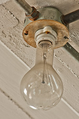 Old clear glass incandescent light bulb still intact. Abandoned Barber-Colman factory in Rockford, Illinois