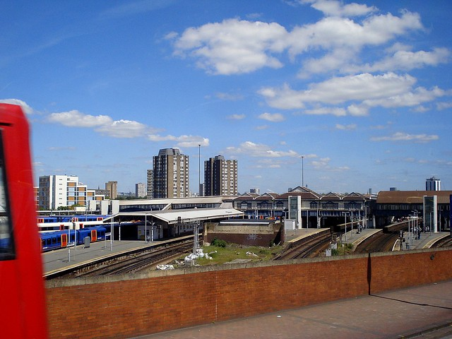 Platforms, lines, and trains at 'Britain's busiest railway station', viewed from the top of a bus on a bridge over the railway lines.  The platforms are open to view.  Tower blocks are visible beyond the station.  A red London bus, also on the bridge, is just beginning to enter the view from the left hand side, making a blurry triangle of bright red.