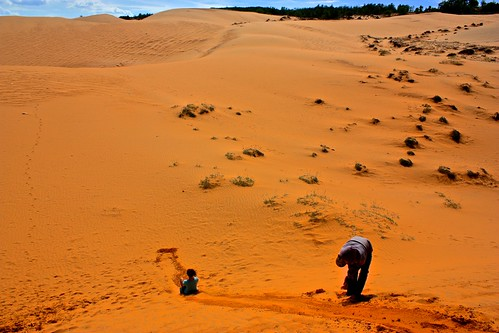 Lina sliding down the red sand dunes