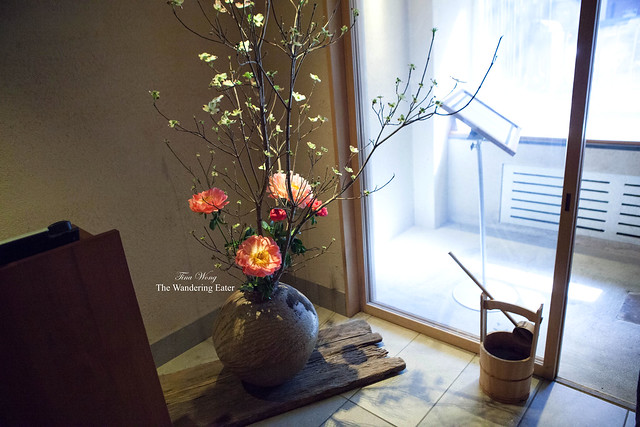 Vase filled with tall floral centerpiece and a wooden bucket near the entry