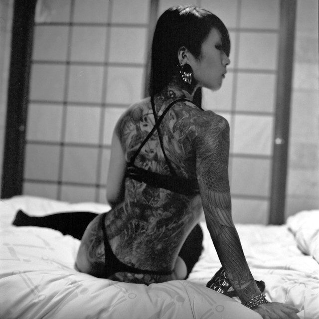 Asian girl, seated on bed, b&w photo