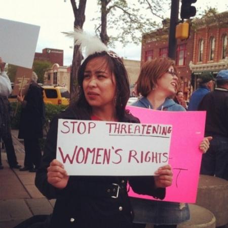 A Native woman holding a protest sign for women's rights