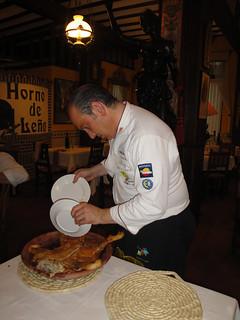 Javier Rodríguez trocea el cochinillo con dos platos.