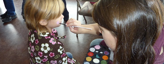 Volunteer face painter painting a pink heart on a young girl's cheek