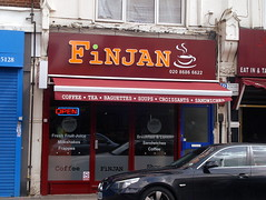 "A small terraced shopfront with a fully-glazed frontage and a sign reading ""Finjan"" in orange on maroon, with a stylised coffee cup in white.  The shopfront itself is in markedly better condition than what can be seen of the upper floor of the building.  The canopy reads: ""Coffee . Tea . Baguettes . Soups . Croissants . Sandwiches""."