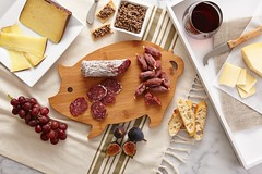 smoked meat salami grapes baguette bread cheese paring knife red wine in a glass spread and pita chip crackers