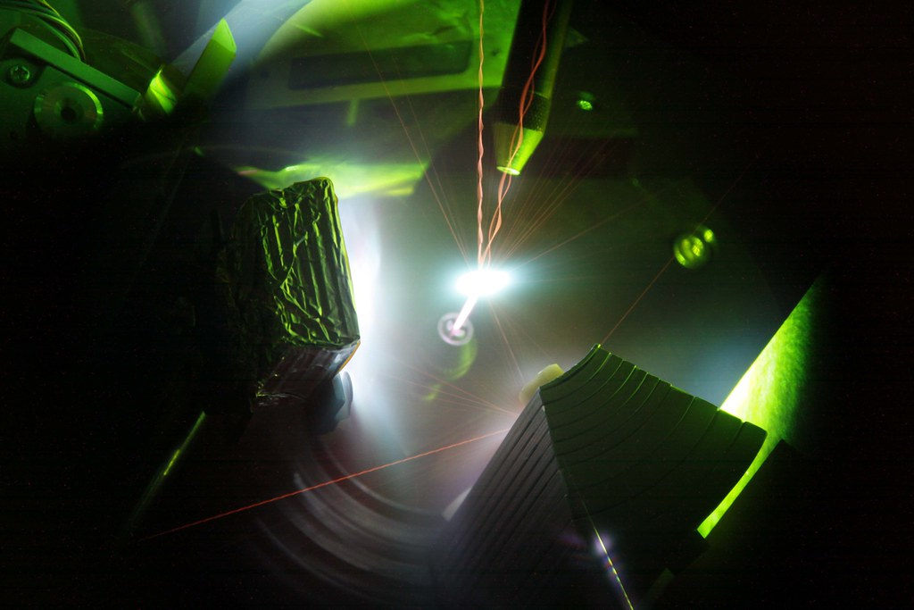 Invisible infrared light from the 200-trillion watt Trident Laser enters from the bottom to interact with a one-micrometer thick foil target in the center of the photo. The laser pulse produces a plasma — an ionized gas — many times hotter than the center of the sun, which lasts for a trillionth of a second. During this time some electrons from the foil are accelerated to virtually the speed of light, and some ions are accelerated to energies of tens of millions of volts. In this time-integrated image, one sees many colorful plasmas that result from the collisions of energetic X-rays and particles with nearby surfaces. Various diagnostic devices located around the edge of the image are illuminated by the plasmas. The green light is caused by the second harmonic of the laser, and is produced by a nonlinear process taking place at the laser-plasma interface (see Chapter Four). Bits of debris from the target are seen as orange streaks of light, some of which ricochet from the surrounding environment, and some of which produce a colorful dance of twisted braids as they spin in flight