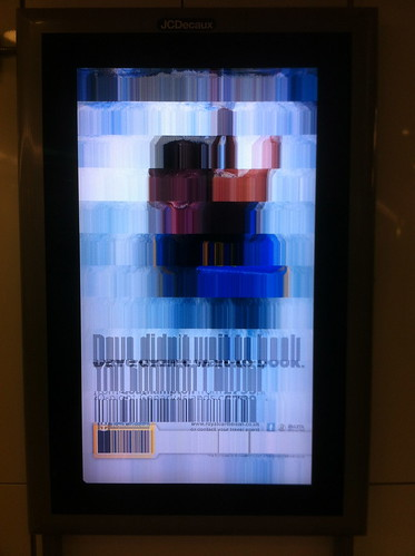 Adverts via broken screen at Stratford station