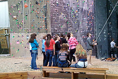 Students from the Talent Search at MSSU wait in line to climb a rock wall.