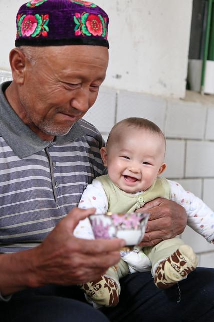 Smiling cute baby at an Uyghur local house, Kumul (Hami) ハミ、ドッパを被ったおじさんと笑顔の赤ちゃん