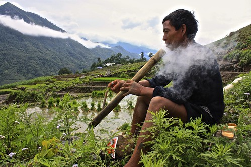 a Hmong man demonstrates his pipe