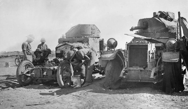 A repair team works on a British armoured car