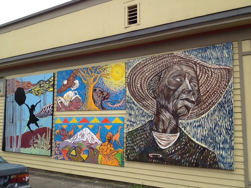 A picture of four large murals painted on the side of a building. The farthest right is of a painting inspired by Catlett's woodcut Sharecropper. It is of a black woman from the shoulders up, wearing a straw hat and looking over her shoulder. She is wearing an expression that is dignified, but tired.