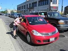 sedan(0.0), automobile(1.0), automotive exterior(1.0), family car(1.0), vehicle(1.0), nissan tiida(1.0), compact car(1.0), nissan(1.0), bumper(1.0), land vehicle(1.0),