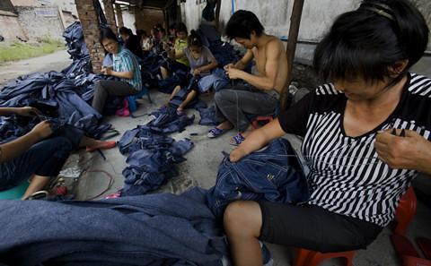 新塘鎮久裕村的打工者在簡易的大棚下加工牛仔褲。這裡隨處可見手工處理牛仔服裝的工人。從早到晚,都有工人把一堆堆牛仔服裝裝上貨車。