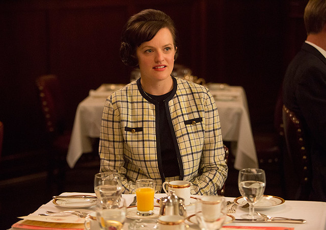 Peggy sits in a restaurant, wearing a white plaid suit